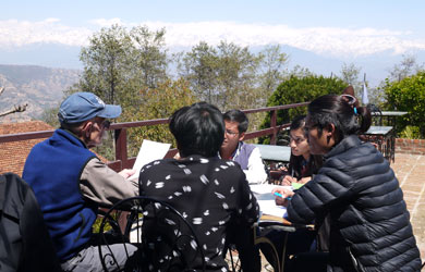 Nepali students with mentors studying on patio deck